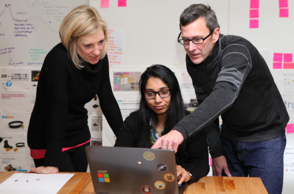 Two professors helping a student with a problem