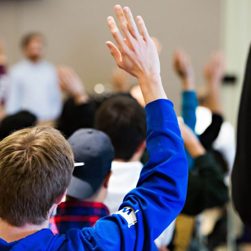 students raising hand in class